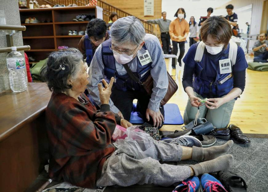 A doctor tends to an elderly woman at an evacuation center in the town of Mashiki, Kumamoto Prefecture, on April 16.