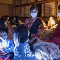 As blackouts continue, a family prepares for another night at an evacuation center in Takamori Town, Kumamoto Prefecture, on April 16. | KYODO