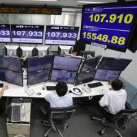 Money traders monitor computer screens with the day's exchange rate between the yen and the U.S. dollar (top right) and Nikkei stock index (bottom right) at a foreign exchange brokerage in Tokyo on Monday. | AP