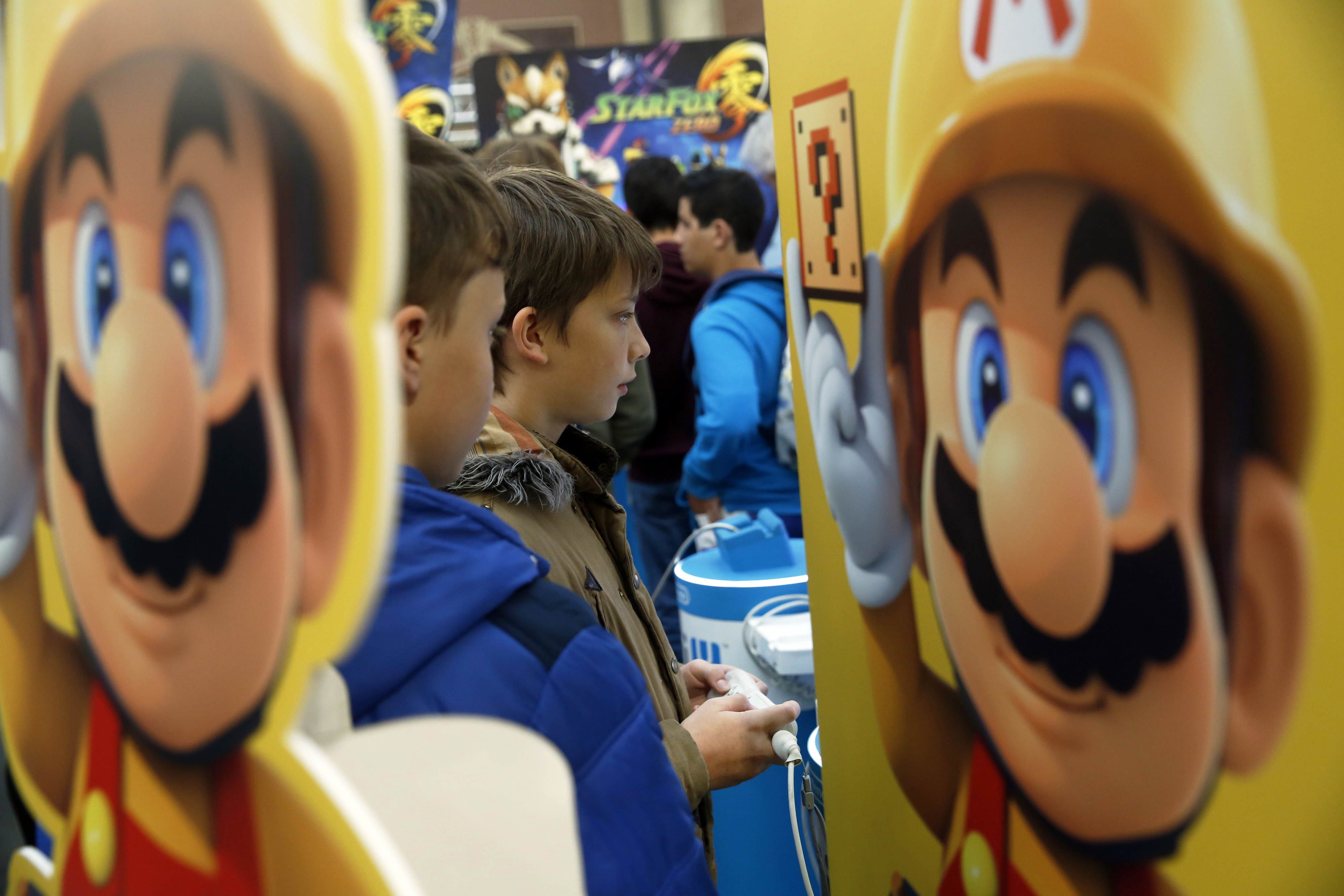 Young visitors to the Legends of Gaming Live event in London play 'Super Mario Maker,' a game developed by Nintendo for the Wii U, in this photo from September.   BLOOMBERG