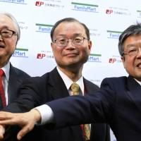 Japan Post Holdings Co. President Masatsugu Nagato (left) poses for a photo with Japan Post Co. President Toru Takahashi (center) and Japan Post Bank Co. President Norito Ikeda during a joint news conference held Tuesday with FamilyMart Co. on their business tieup in Tokyo. | REUTERS