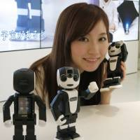 A woman poses with Sharp's humanoid RoBoHon smartphone on Thursday at a Sharp's Tokyo office. The product hits stores on May 26.   KAZUAKI NAGATA
