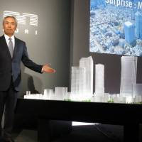 Mori Building CEO Shingo Tsuji poses in front of a model of his firm's redevelopment plan for the Toranomon area of Tokyo on Wednesday in the capital. | KAZUAKI NAGATA
