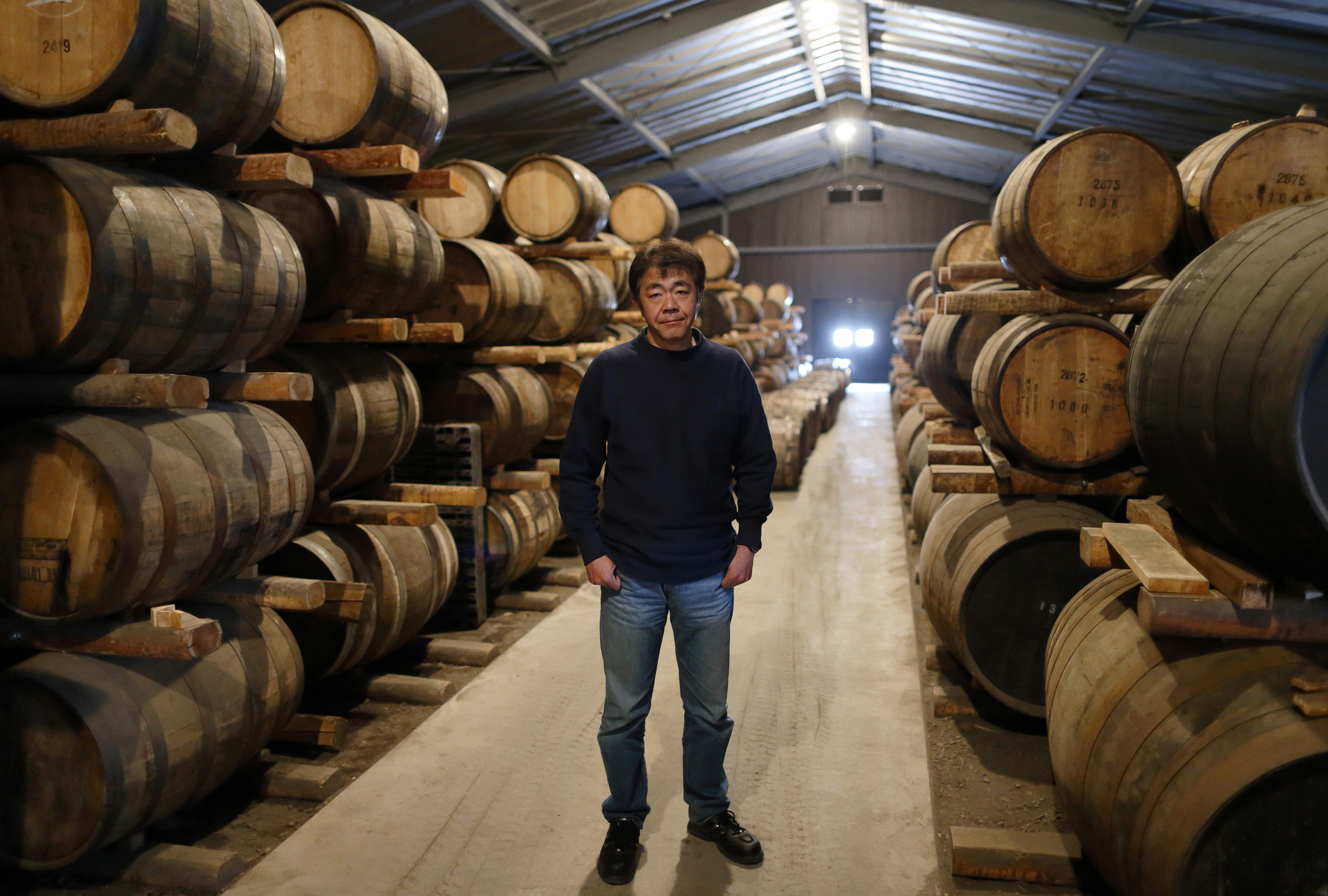 Ichiro Akuto shows off barrels of whisky at his distillery, Venture Whisky Ltd., in Chichibu, Saitama Prefecture. His single malts sell for as much as ¥100,000 a bottle. | BLOOMBERG