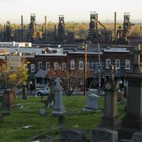 The blast furnaces of the now-closed Bethlehem Steel mill sit behind row houses and a cemetery in Bethlehem, Pennsylvania, Thursday. After Bethlehem Steel's blast furnaces went silent 20 years ago in the city of Bethlehem, the local economy bounced back as new industrial parks filled with e-commerce companies and white-collar businesses fleeing New York's higher costs. | REUTERS