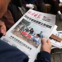 A man reads a newspaper featuring a front-page photo of Chinese leadersm including President Xi Jinping (center), attending a tree-planting ceremony, at a news stand in Beijing on Wednesday. Chinese media have largely avoided reporting on revelations about China's leaders included in the 'Panama Papers' leaks and social media have been scrubbed of references to them.   AFP-JIJI