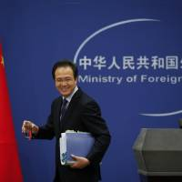 Foreign Ministry spokesman Hong Lei smiles as he leaves the stage after giving a news briefing at the Ministry of Foreign Affairs in Beijing Tuesday. The ministry denounced as 'groundless' reports based on documents leaked from a Panama-based law firm that name relatives of current and retired Chinese politicians, including President Xi Jinping, as owning offshore companies. Hong said he would not further discuss the reports and declined to say whether the individuals named would be investigated.   AP