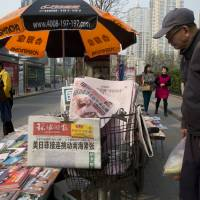 A man looks at a newsstand with a copy of the day's Global Times displayed on a basket in Beijing Tuesday. The nationalistic tabloid Global Times published an editorial saying an unidentified 'powerful force' was behind the documents leaked from a Panama-based law firm that name relatives of current and retired Chinese politicians, including President Xi Jinping, as owning offshore companies.   AP