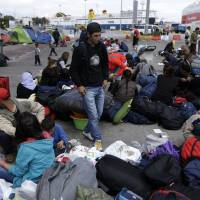 Migrants with their belongings wait for a bus transporting them to government-built shelters from the Athens port of Piraeus on Monday. More than 53,000 people who made their way to Greece from Turkey have been stranded in the country since Balkan and European nations shut their land borders to stem the largest refugee flow the continent has seen since World War II. | AP
