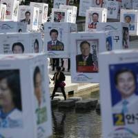 Candidates' posters for upcoming general elections are seen hanging over the Cheonggye stream in downtown Seoul on Monday. | AP