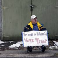 Tom Kennedy of Schenectady, New York, holds a sign across the street from where Republican presidential candidate, Sen. Ted Cruz is scheduled to hold a campaign event Thursday at Mekeel Christian Academy in Scotia. | AP