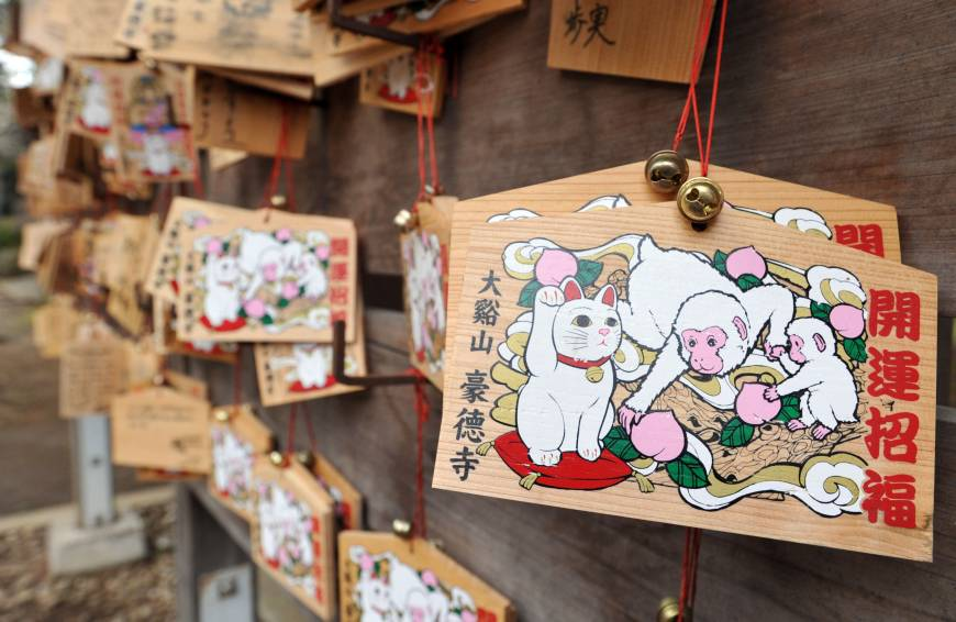 Wooden prayer tablets decorated with images of a beckoning cat and a monkey, this year