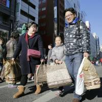 Chinese tourists shop in Tokyo's Ginza district on Feb. 7. | KYODO