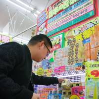 A Chinese tourist buys goods at a Don Quijote Co. discount store in Tokyo's Shinjuku Ward on Feb. 16. | KYODO