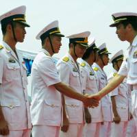 Maritime Self-Defense Force Capt. Haruhiko Morishita (right), the commander of the 15th Escort Division, greets Vietnamese Navy officers during a welcoming ceremony for two Japanese guided-missile destroyers at Cam Ranh Bay in Vietnam on Tuesday. | AFP-JIJI