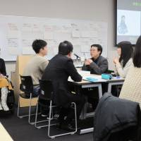 Participants discuss ways to remove social barriers for people with disabilities as moderator Ryoko Yamazaki (far left) looks on at a Keio University campus in Yokohama in February. | KYODO