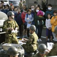 Evacuees line up for food distributed by Self-Defense Forces personnel on Friday at the town office in Mashiki, Kumamoto Prefecture. | KYODO