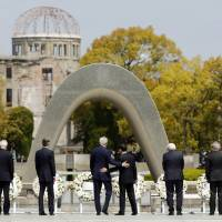 U.S. Secretary of State John Kerry puts his hand on Foreign Minister Fumio Kishida's back after they and their fellow Group of Seven foreign ministers laid wreaths at the cenotaph at Hiroshima Peace Memorial Park on Monday. Also pictured (left to right) are EU High Representative for Foreign Affairs Federica Mogherini, Canadian Foreign Minister Stephane Dion, British Foreign Secretary Philip Hammond, German Foreign Minister Frank-Walter Steinmeier, Italian Foreign Minister Paolo Gentiloni and French Foreign Minister Jean-Marc Ayrault. | POOL / AP