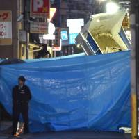 A police officer stands guard after a truck rammed a Kobe Yamaguchi-gumi office in the city on March 19. | KYODO