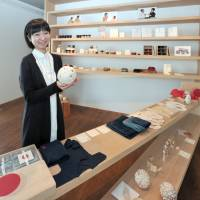 Rika Yajima poses with traditional crafts sold at her aeru store in Tokyo's Meguro district in March. | YOSHIAKI MIURA