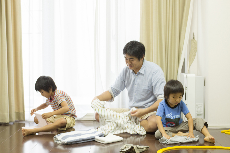 At-home-dad Taizo Horikomi folds laundry together with his sons in October. | COURTESY OF TAIZO HORIKOMI