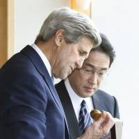 U.S. Secretary of State John Kerry looks at a watch presented by Foreign Minister Fumio Kishida ahead of their meeting in Hiroshima on Monday. | POOL / KYODO