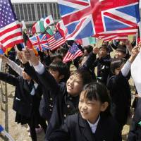Schoolchildren hold flags representing the Group of Seven nations as their foreign ministers visited Hiroshima Peace Memorial Park on Monday. | AP