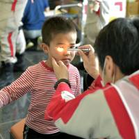 A boy receives care from a doctor at a temporary shelter set up at a gym in Mashiki, Kumamoto Prefecture, on Sunday.