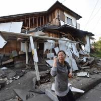 A couple head home past a severely damaged house in Mashiki, Kumamoto Prefecture, on Saturday. | AFP-JIJI