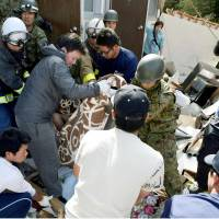 Self-Defense Force servicemen rescue a student from a collapsed apartment in the village of Minamiaso on Saturday morning. | KYODO