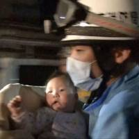 A rescue worker holds an 8-month-old baby pulled from the rubble early Friday. | KUMAMOTO PREFECTURAL POLICE / KYODO