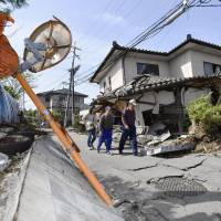 Residents survey damaged roads and toppled houses in the town of Mashiki, Kumamoto Prefecture, on Friday. | KYODO