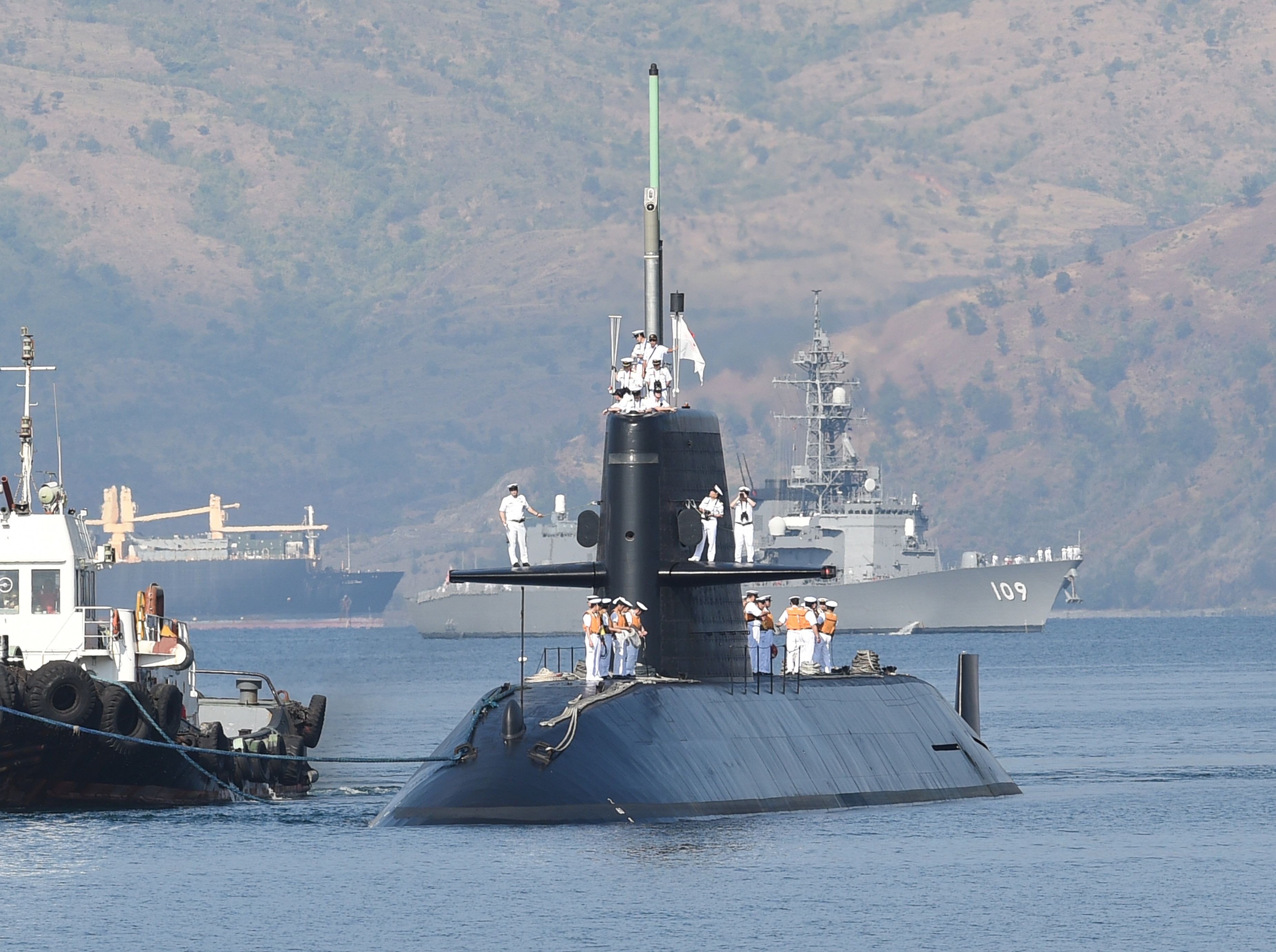 The Maritime Self-Defense Force training submarine Oyashio, escorted by the destroyer Ariake (background), one of two vessels that accompanied the sub, arrives at Subic Bay in the Philippines on Sunday. | AFP-JIJI