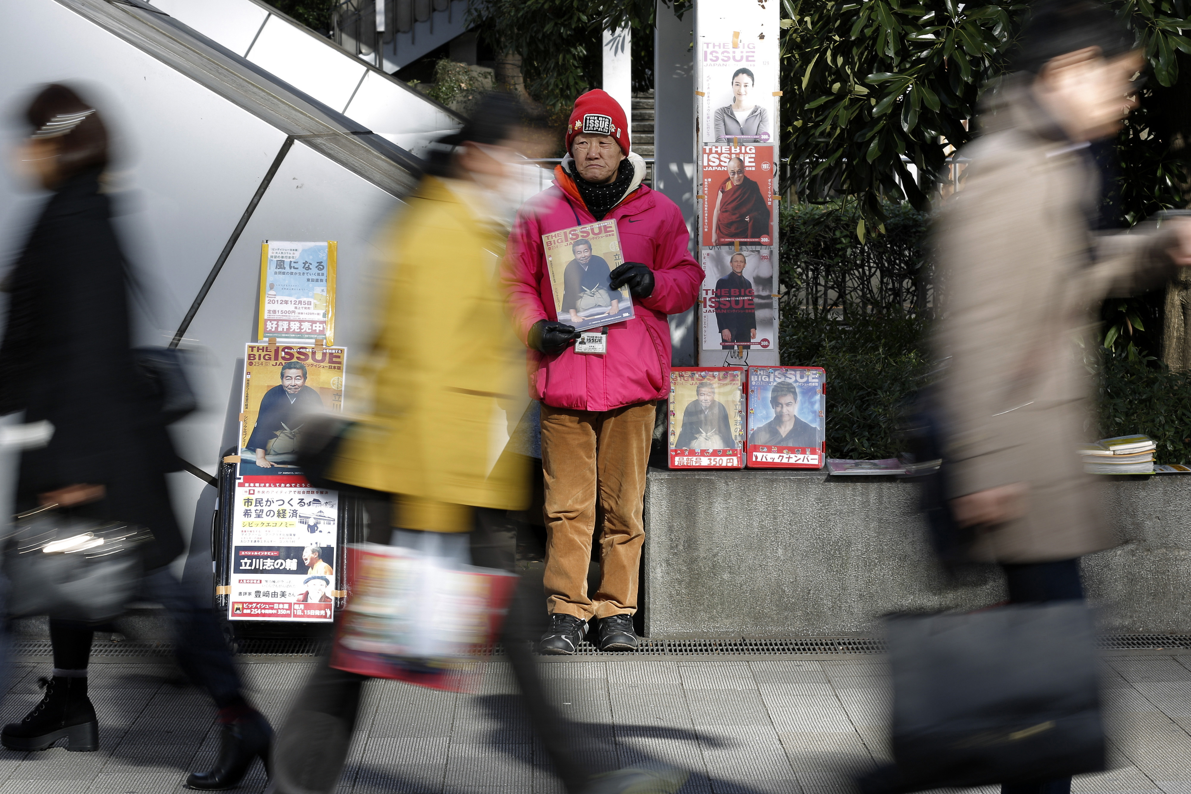 Homeless Toyoji Yoshizawa sells copies of the Big Issue Japan magazine on a Tokyo street in January 2015. Experts say income disparity has widened under Prime Minister Shinzo Abe, leaving a larger portion of the population, especially the young, below the poverty line. | BLOOMBERG