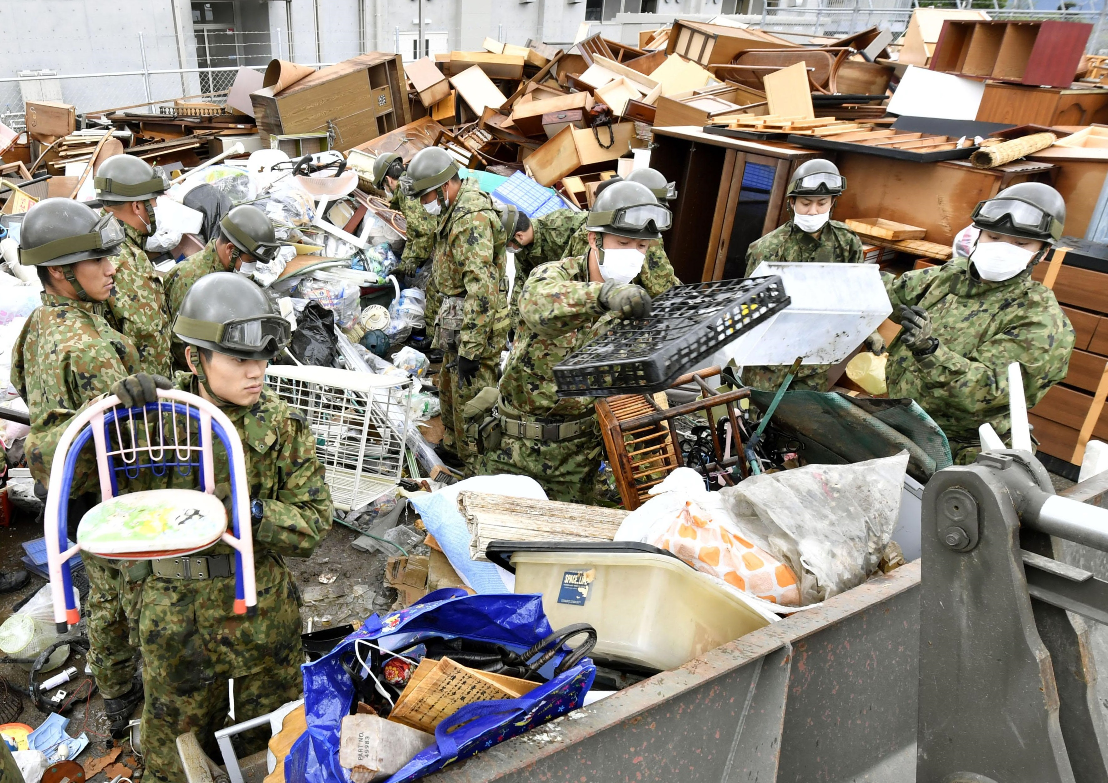 Self-Defense Forces members collect piled-up waste and debris from streets in the quake-hit city of Kumamoto on Thursday. | KYODO