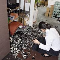 A woman sifts through broken crockery in a restaurant in Kumamoto's Chuo Ward Thursday night after a strong quake hit the area.  | KYODO