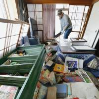 A man begins cleaning up his house Friday in the town of Mashiki after a bookshelf toppled.  | KYODO