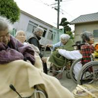 Elderly people wait in their wheelchairs outside a welfare facility in the town of Mashiki, Kumamoto Prefecture, on Sunday morning. They were unable to enter the center due to the fact that many people who had sought shelter there after deadly earthquakes which hit late Thursday and early Saturday were already inside. | KYODO