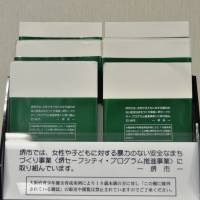 Green book covers wrapped around sample books on a store shelf say the city of Sakai is promoting measures to eradicate violence against women and children. | SAKAI MUNICIPAL GOVERNMENT