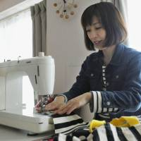 Nami Uchiyama, a 39-year-old graphic designer in Tokyo, sews a bag for her son at her home in Setagaya Ward on March 14 before he begins elementary school this month. | KYODO