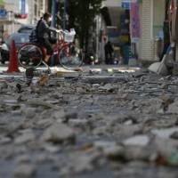A cyclist passes by the debris at an arcade street in Kumamoto city on April 17, 2016. | AP