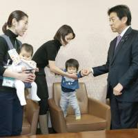 Mothers meet welfare minister Yasuhisa Shiozaki at the Diet in March to hand him a petition calling for an increase in day care centers. | KYODO