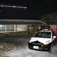 A police officer guards a house in Kato, Hyogo Prefecture, where a 79-year-old woman was found strangled Tuesday. | KYODO