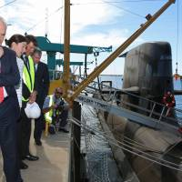 Australian Prime Minister Malcolm Turnbull) looks at a Collins-class submarine at a naval shipyard in Adelaide on Tuesday after announcing that French contractor DCNS bested rivals from Germany and Japan for a multibillion dollar contract to design and build Australia's next generation of submarines. | AFP-JIJI