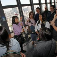 A guide addresses tourists inside Tokyo Tower during a tour operated by Hato Bus Co. in November 2015. As Japan seeks to lure more foreign visitors, the tour guide industry is in flux. | BLOOMBERG