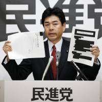 Opposition lawmaker Kazunori Yamai of the Democratic Party shows reporters a redacted record of TPP negotiations on Wednesday in the Diet. | KYODO