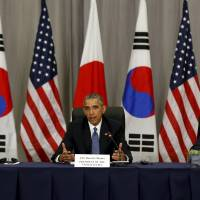 U.S. President Barack Obama takes part in a trilateral meeting with South Korean President Park Geun-hye (left) and Prime Minister Shinzo Abe on the fringes of the Nuclear Security Summit in Washington on Thursday. | REUTERS