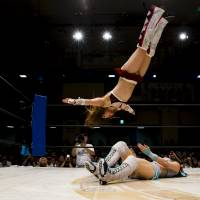 Io Shirai (top) performs a moonsault onto Mayu Iwatani during their Stardom professional wrestling show at Korakuen Hall in Tokyo in July 2015. | REUTERS