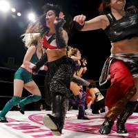 Wrestler Kris Wolf (center) and fellow wrestlers scatter across the ring during their wrestling show in Tokyo. | REUTERS
