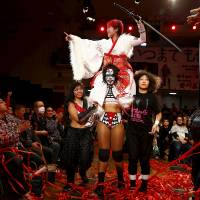 Wrestlers Kris Wolf and Kimura Kyoko carry their fellow fighter Act Yasukawa after her last match before retirement on Dec. 23, 2015. | REUTERS